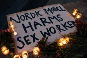Candles around a sign, sign reads 'Nordic model harms sex workers'