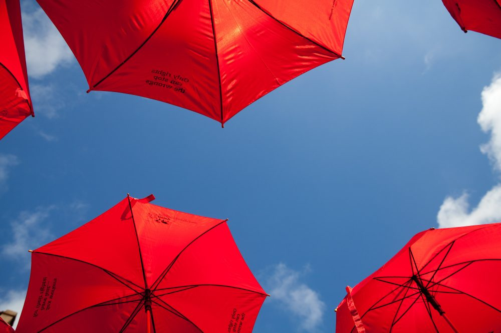 an image of a blue sky framed by the undersides of red umbrellas